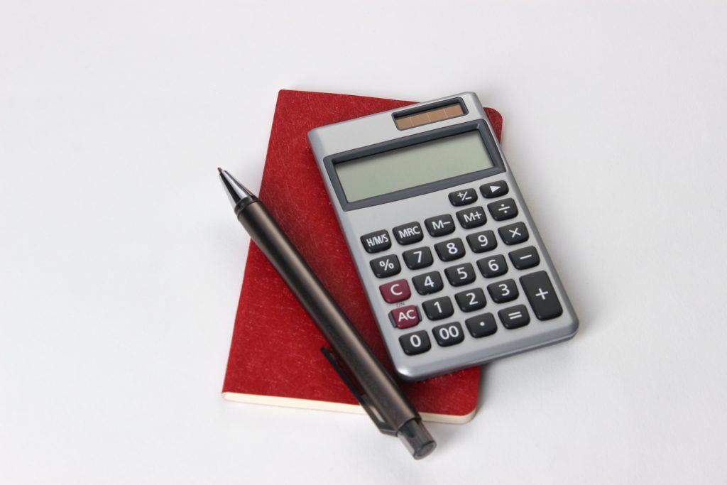 Calculador, lápiz y papel para determinar cuánto dinero debe devolver CaixaBank al reclamar los gastos de la hipoteca