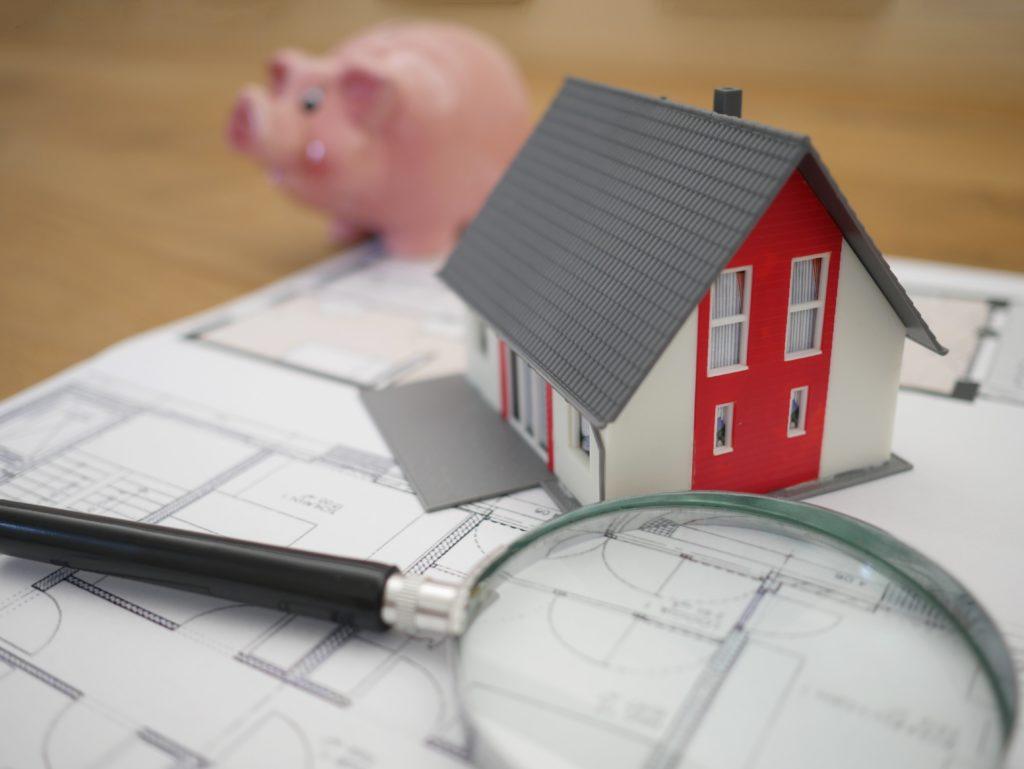 Casa miniatura y lupa sobre plano estructural
