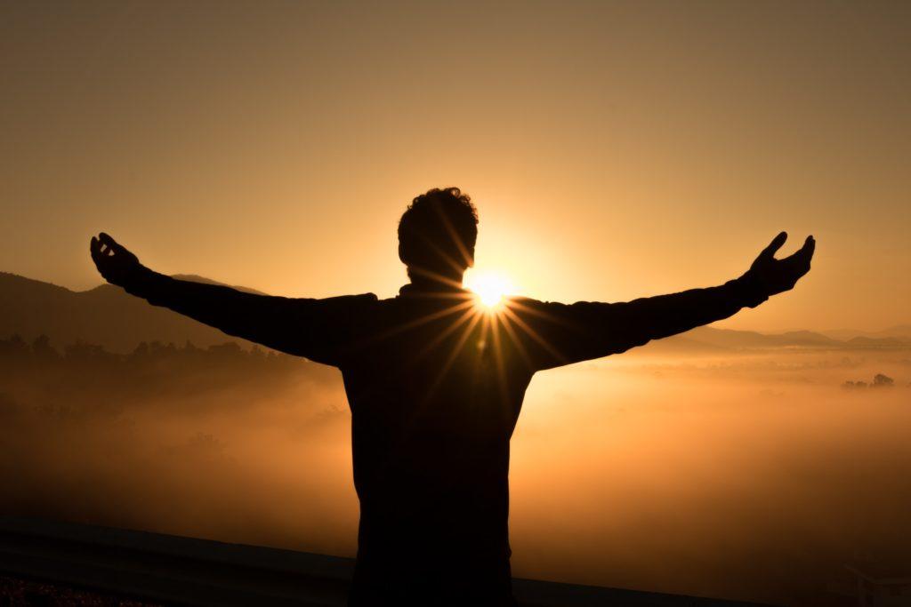 Persona con los brazos abiertos frente al sol