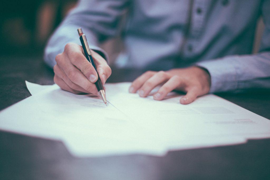 Persona firmando la solicitud del concurso de acreedores voluntario