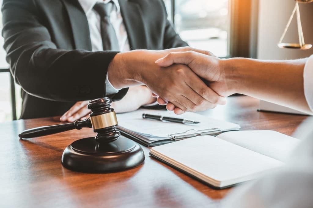 Dos personas estrechando las manos sobre un escritorio y un martillo de juez