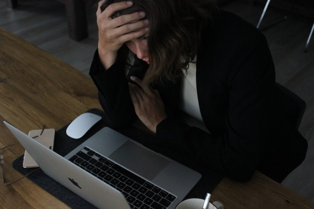 Persona preocupada frente a un laptop