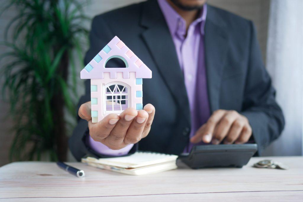 Persona sosteniendo una casa en miniatura