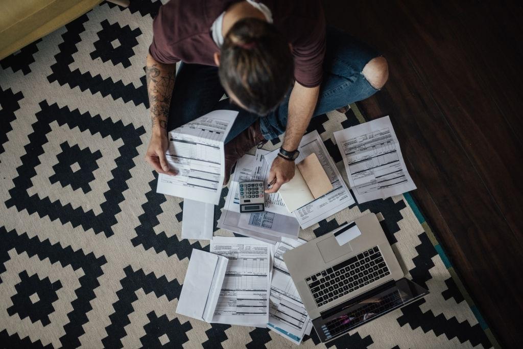 Persona sentada en el suelo con calculador y documentos