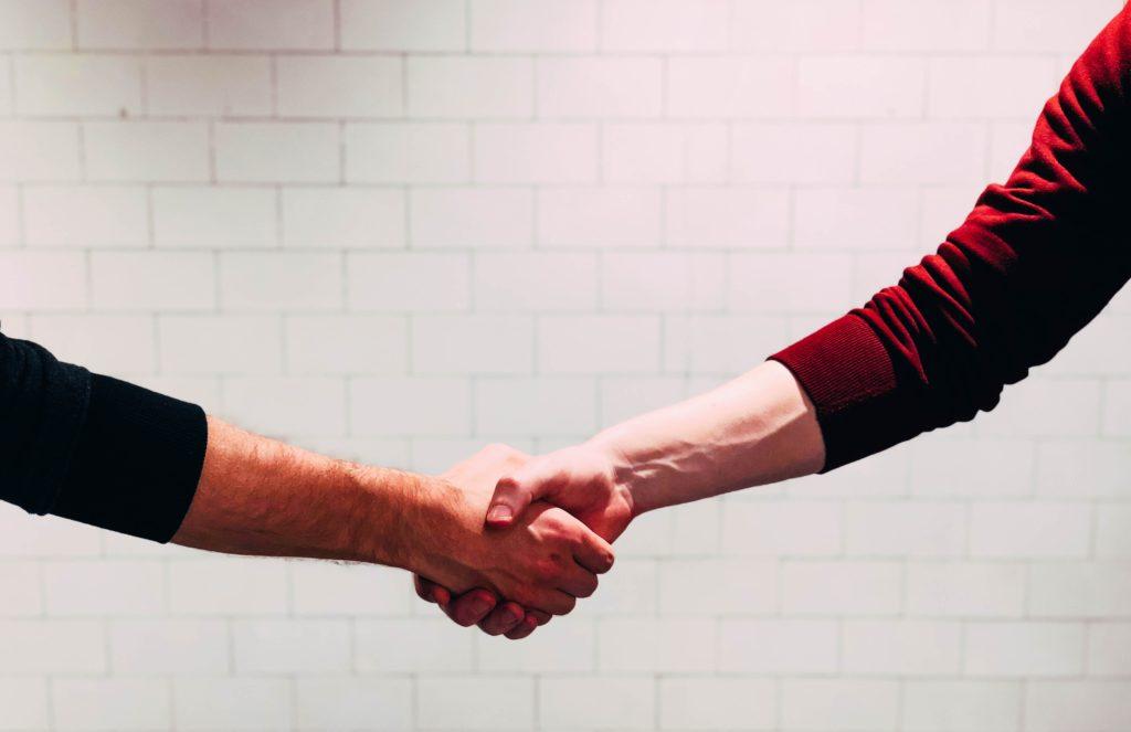 Dos personas estrechando sus manos
